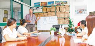 三亚外教英语课走进旅行社三亚昊利德国际旅行社有限公司会议室内,加拿大籍外教卡梅伦正在给公司员工进行英语口语日常交流培训。