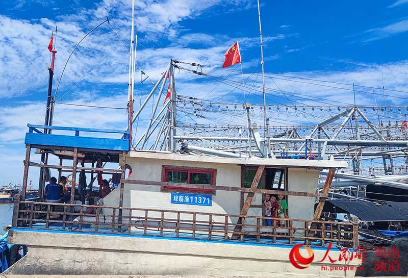 临近出海,大人们坐在甲板上聊天,孩子在渔船上嬉戏。人民网 牛良玉摄