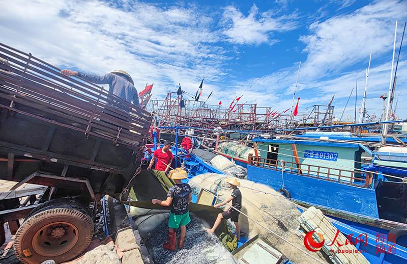 渔民合力将冰块送入船舱内。人民网 牛良玉摄